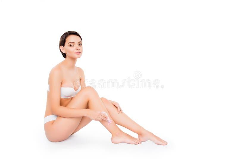 Jong mooi meisje die in lingerie haar die benen met scheermes scheren op witte schone duidelijke achtergrond wordt geïsoleerd Lic stock foto