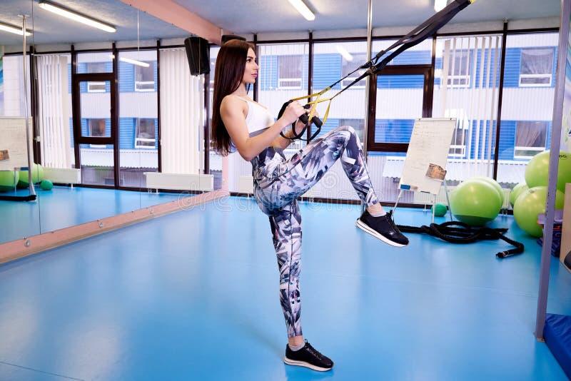 Jong mooi meisje die met geschiktheidsriemen uitoefenen in de gymnastiek stock afbeelding