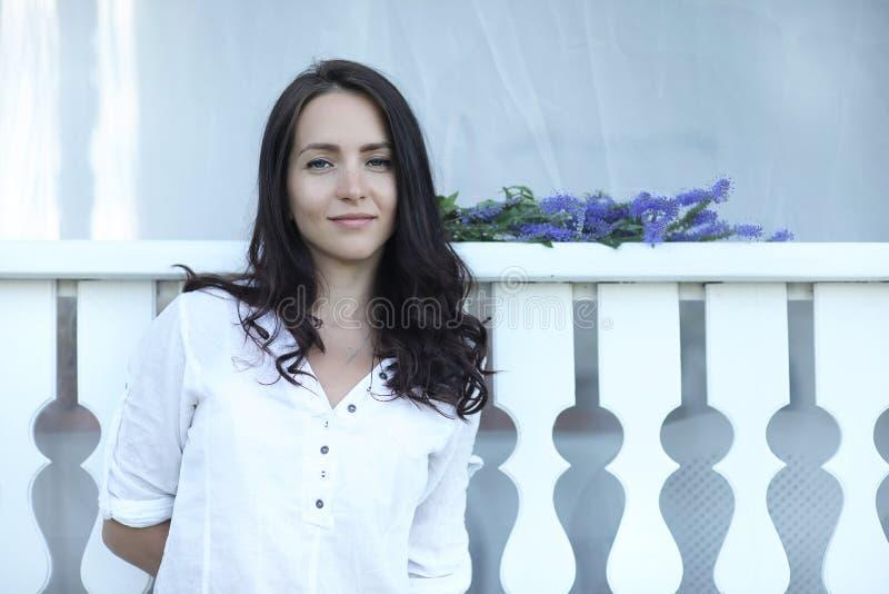 Jong mooi meisje die met lang donkerbruin haar in uitstekende zwarte kleding in witte erwten dichtbij blokhuis in dorp zitten stock afbeeldingen