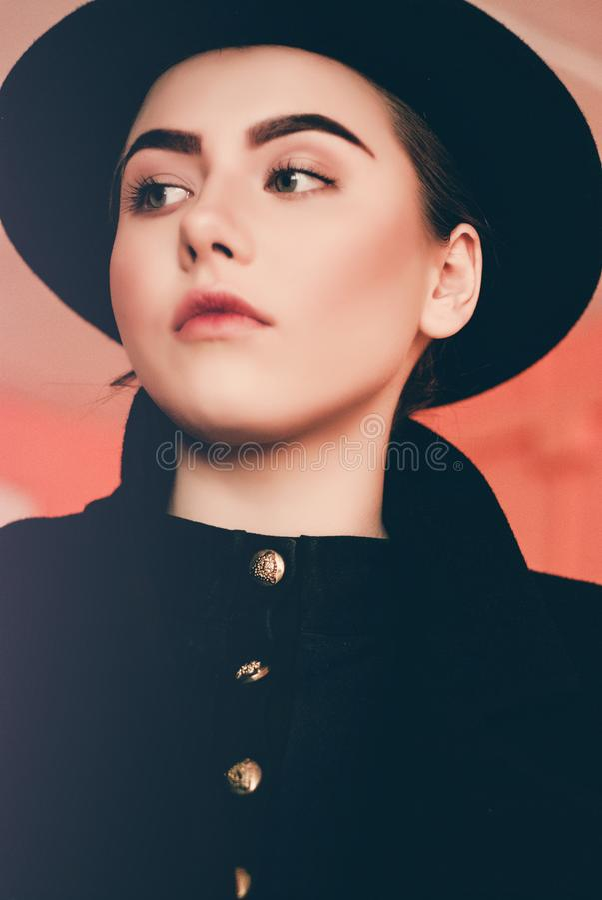 Jong mooi meisje die met perfecte samenstelling, een zwarte hoed en een laag dragen royalty-vrije stock foto's
