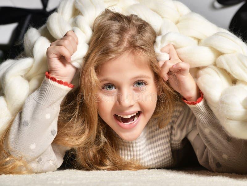 Jong mooi meisje die onder grote met de hand gemaakte merinoswol witte bla liggen stock fotografie