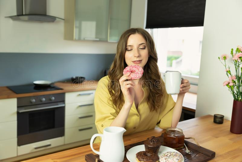Jong mooi meisje die ontbijt thuis in de keuken hebben royalty-vrije stock afbeelding