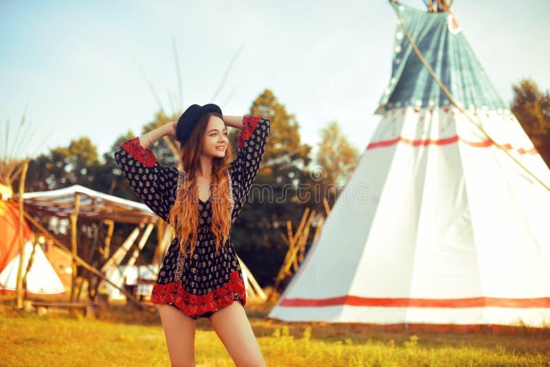 Jong mooi meisje die op achtergrondtipi, tipi inheems Indisch huis glimlachen Mooi meisje in hoed met lang cerly haar stock afbeeldingen