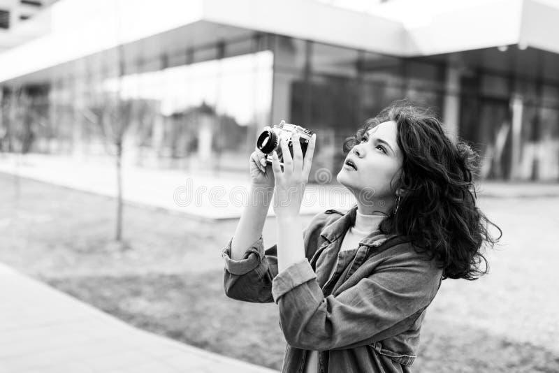 Jong mooi meisje die op de straat, gekleed in jeans en denimoverhemd lopen Studentenweekdagen Het leuke meisje houdt de camera va stock afbeeldingen