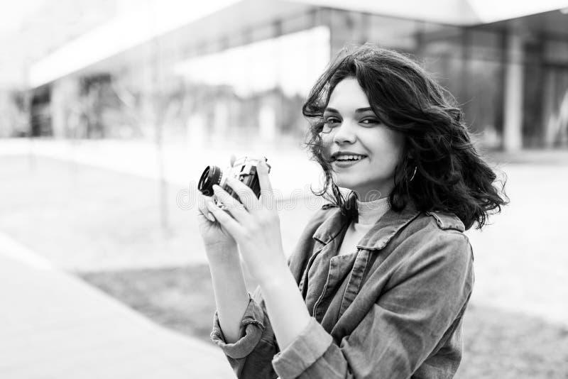 Jong mooi meisje die op de straat, gekleed in jeans en denimoverhemd lopen Studentenweekdagen Het leuke meisje houdt de camera va royalty-vrije stock afbeeldingen
