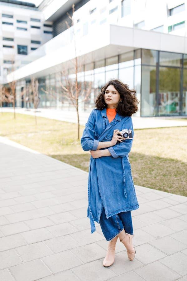 Jong mooi meisje die op de straat, gekleed in jeans en denimoverhemd lopen Studentenweekdagen Het leuke meisje houdt de camera va royalty-vrije stock afbeelding
