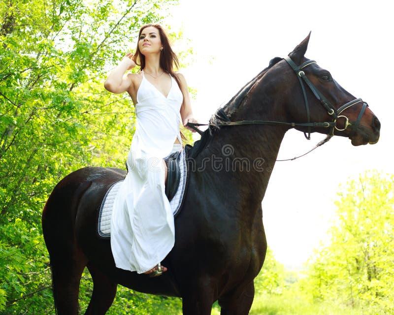 Jong mooi meisje die op paard berijden stock foto's