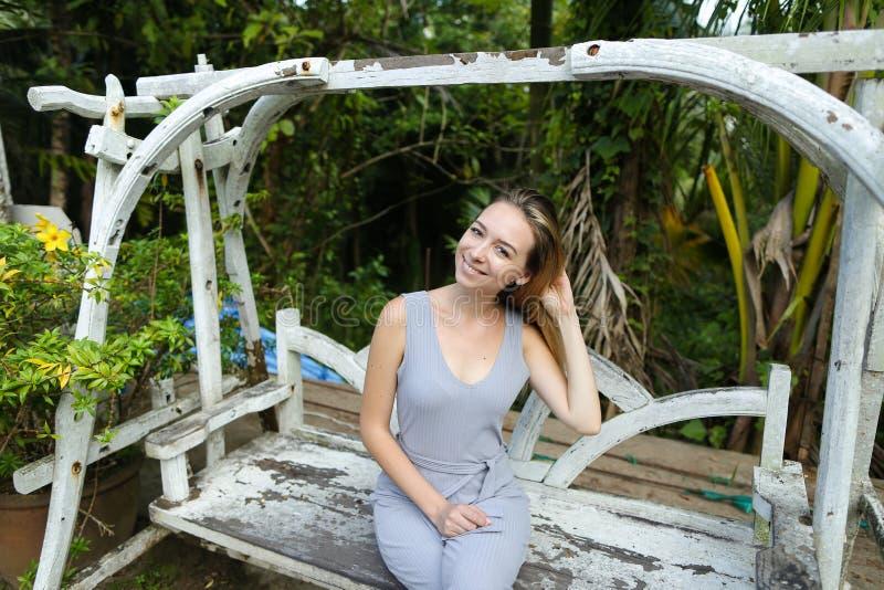 Jong mooi meisje die op schommeling in exotische tuin, palmen op achtergrond berijden stock fotografie