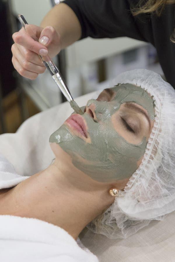 Jong mooi meisje die opheffend gezichtsmasker in de salon van de kuuroordschoonheid ontvangen - binnen stock afbeelding