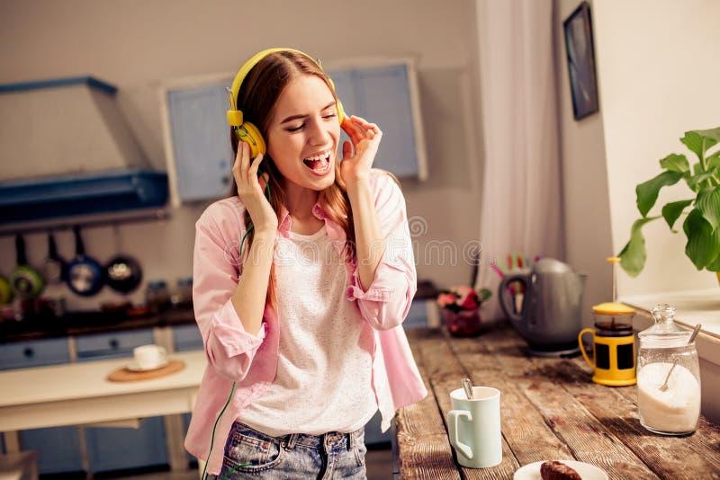 Jong mooi meisje die pret hebben die aan muziek in hoofdtelefoons luisteren royalty-vrije stock fotografie