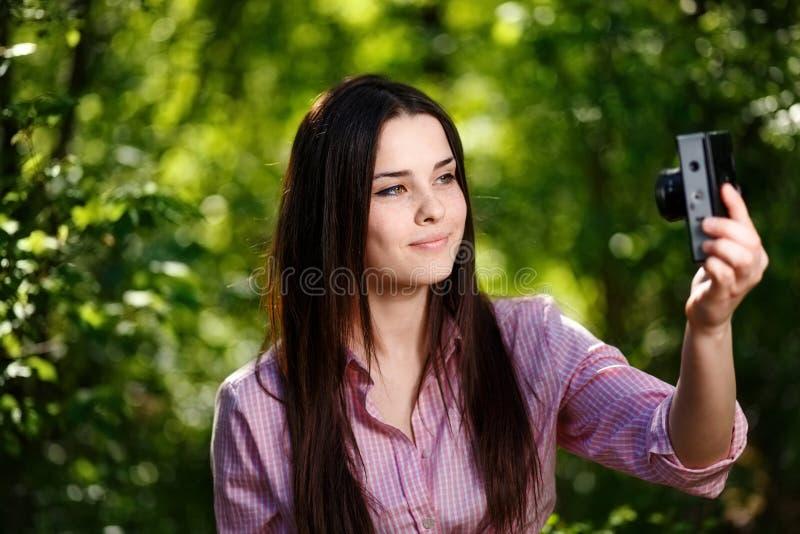 Jong mooi meisje die selfie met retro filmcamera nemen stock foto's