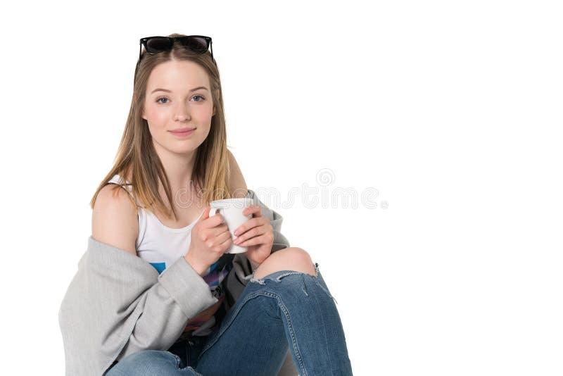 Jong mooi meisje die in vrijetijdskleding een kop van iets houden aan drank, geïsoleerd studioschot, zuivere witte achtergrond royalty-vrije stock foto's