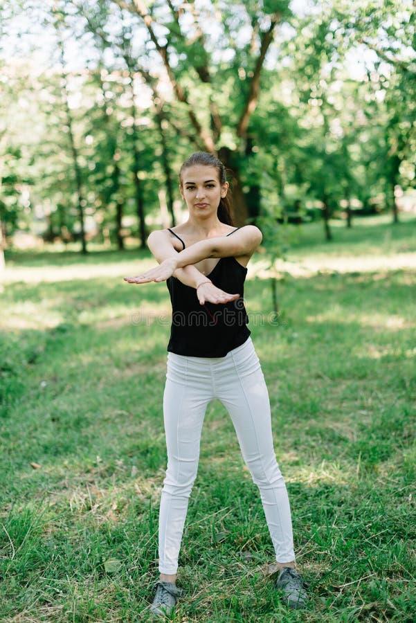 Jong mooi meisje die yoga in openlucht in het park doen stock afbeelding