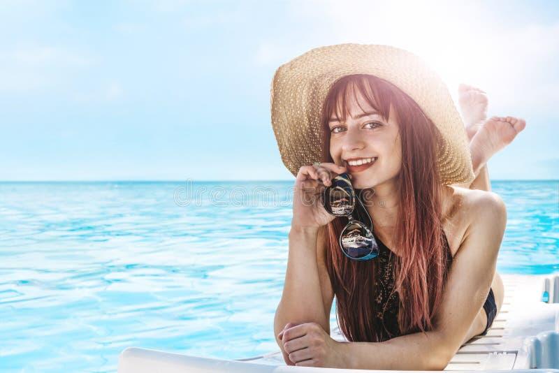 Jong mooi meisje die in zon in een hoed en het zonnebaden liggen Verre tropische stranden en landen reis concept Toerist royalty-vrije stock afbeeldingen