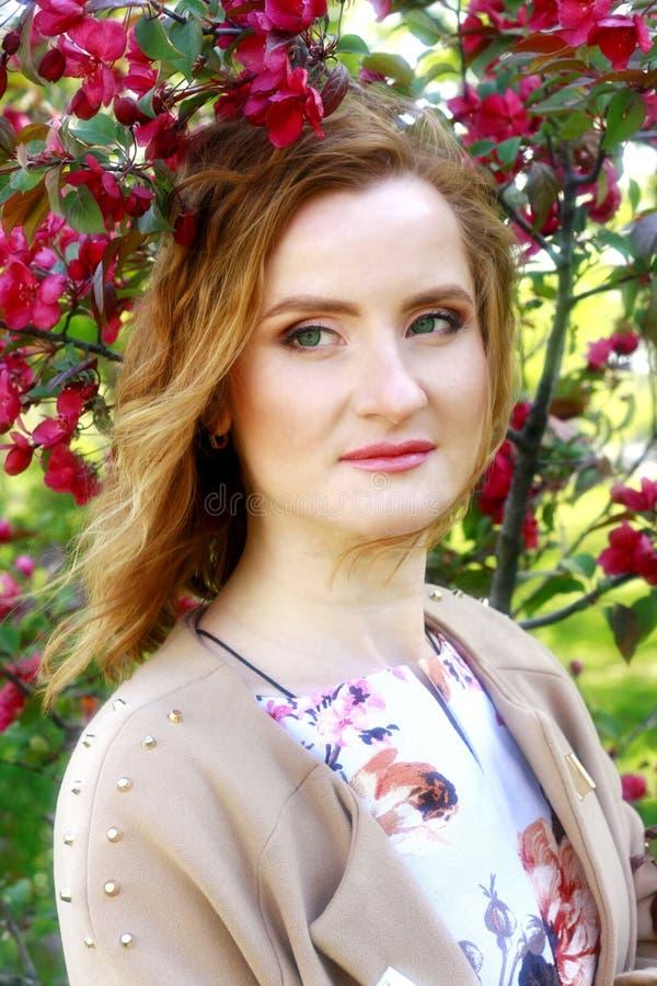 Jong mooi meisje in een appelboomgaard Het portret van het roodharige meisje royalty-vrije stock fotografie