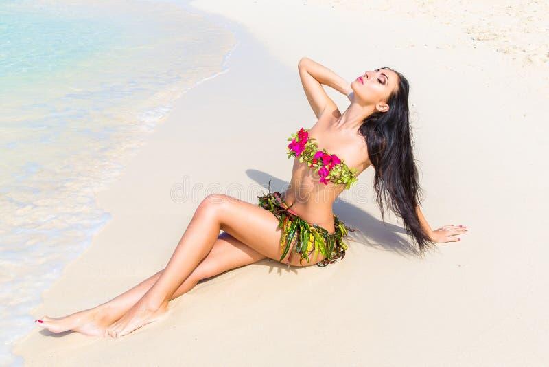 Jong mooi meisje in een bikini van bloemen op tropische beac royalty-vrije stock fotografie