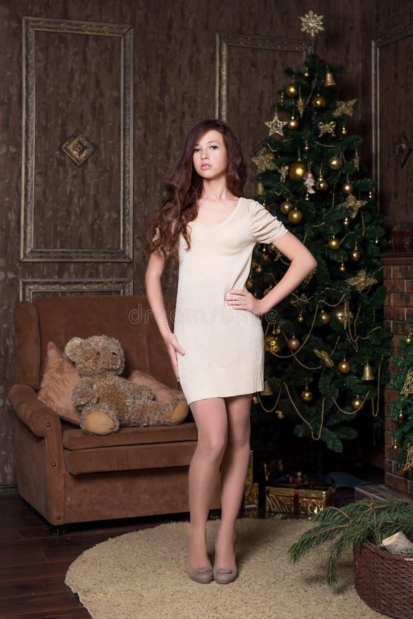 jong mooi meisje in een gouden uitstekende retro kleding die zich in een ouderwetse woonkamer met een nieuwe jaarboom bevinden stock foto