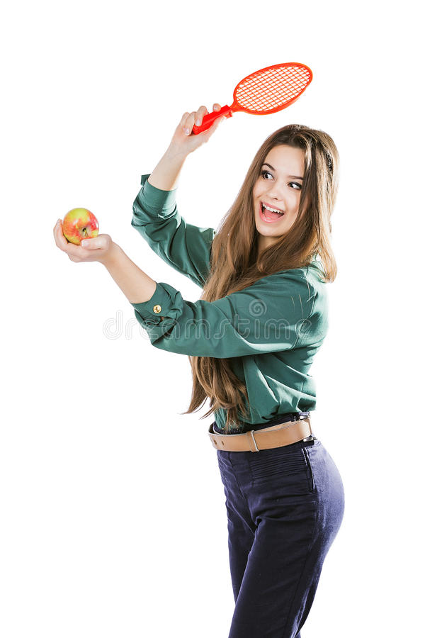Jong mooi meisje in een groene blouse die een appel met tennisracket het glimlachen houden Apple wil de racket raken isoleer stock foto