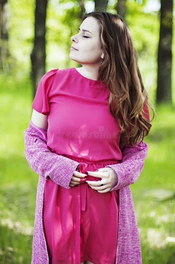 Jong mooi meisje in een roze laag en roze korte kledingslaarzen r stock afbeeldingen