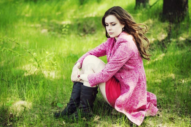 Jong mooi meisje in een roze laag en roze korte kledingslaarzen r royalty-vrije stock fotografie
