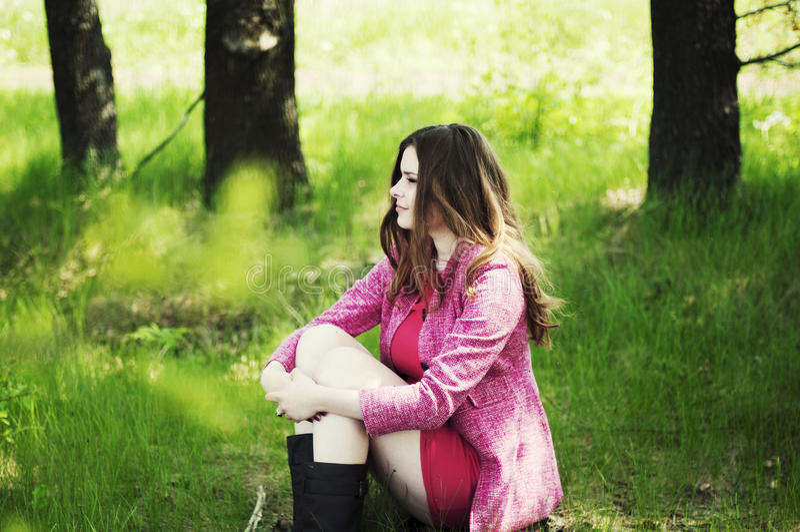 Jong mooi meisje in een roze laag en roze korte kledingslaarzen r royalty-vrije stock afbeelding