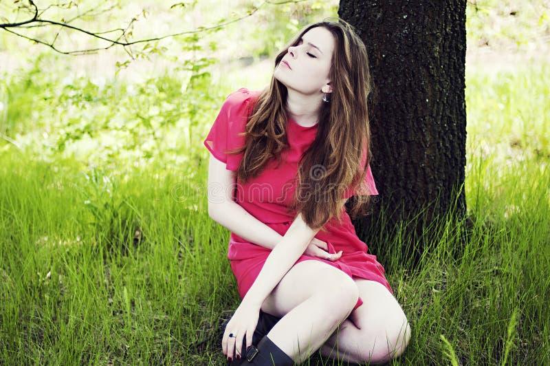 Jong mooi meisje in een roze laag en roze korte kledingslaarzen r royalty-vrije stock foto