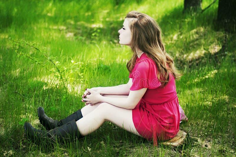Jong mooi meisje in een roze laag en roze korte kledingslaarzen r stock afbeelding