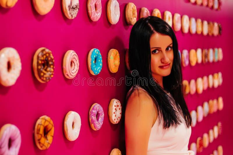 Jong mooi meisje in een witte kleding op een roze achtergrond van multi-colored donuts stock foto