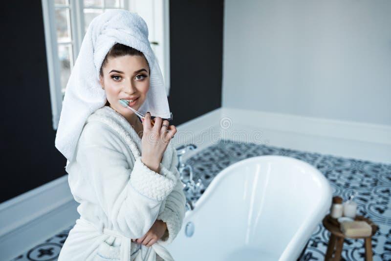 Jong mooi meisje in een witte peignoir en handdoek op haar hoofd die haar tanden borstelen terwijl het baden in de badkamers royalty-vrije stock foto