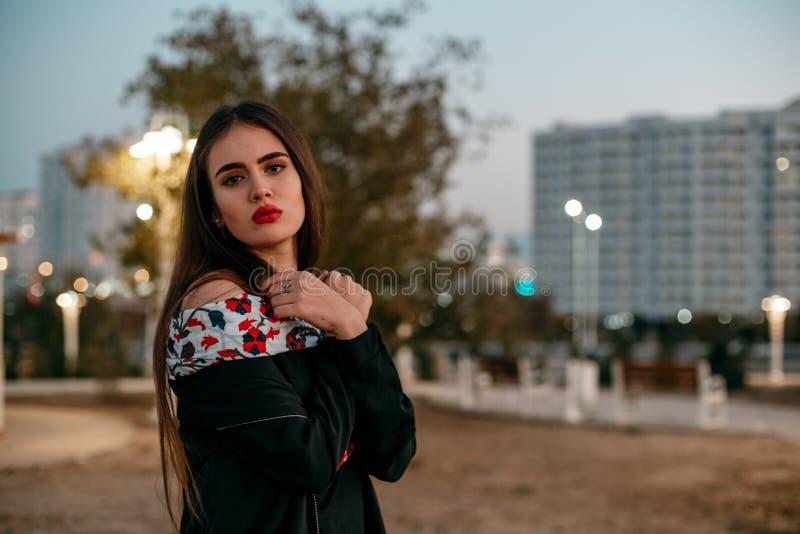 Jong mooi meisje in een zwart jasje met sjaal het stellen in de avond op de straat stock foto