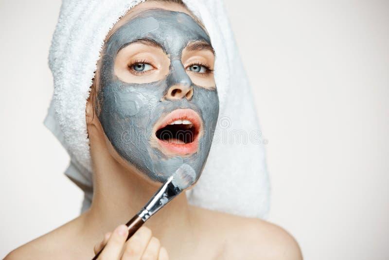 Jong mooi meisje in handdoek op hoofd die gezicht behandelen met masker die camera met geopende mond over witte achtergrond bekij stock fotografie