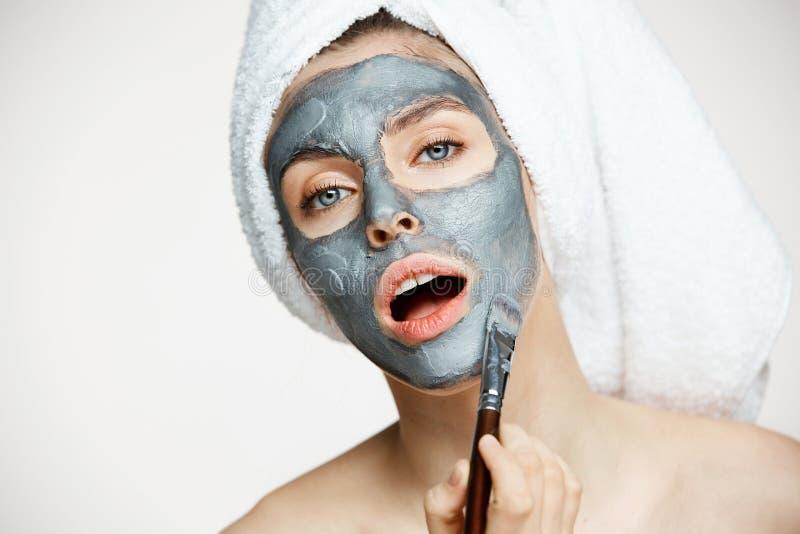 Jong mooi meisje in handdoek op hoofd die gezicht behandelen met masker die camera met geopende mond over witte achtergrond bekij stock foto