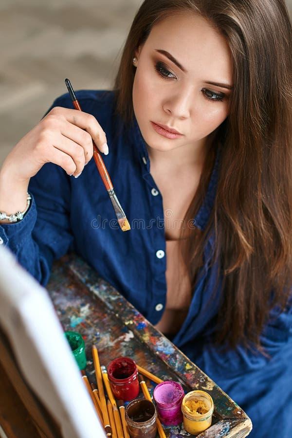 Jong mooi meisje, het vrouwelijke kunstenaarsschilder denken aan een nieuw kunstwerk en klaar om de eerste penseelstreek te maken royalty-vrije stock afbeelding