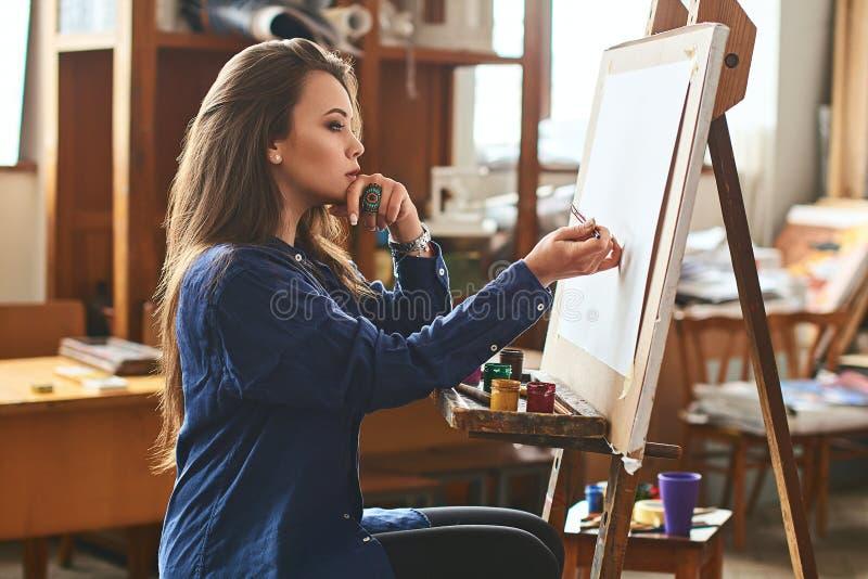 Jong mooi meisje, het vrouwelijke kunstenaarsschilder denken aan een nieuw kunstwerkidee en klaar om de eerste penseelstreek te m stock fotografie