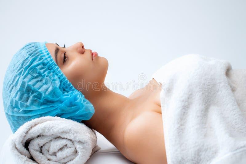 Jong mooi meisje in kuuroordsalon Het meisje ligt op de laag voor een massage na een verjongingsprocedure stock fotografie