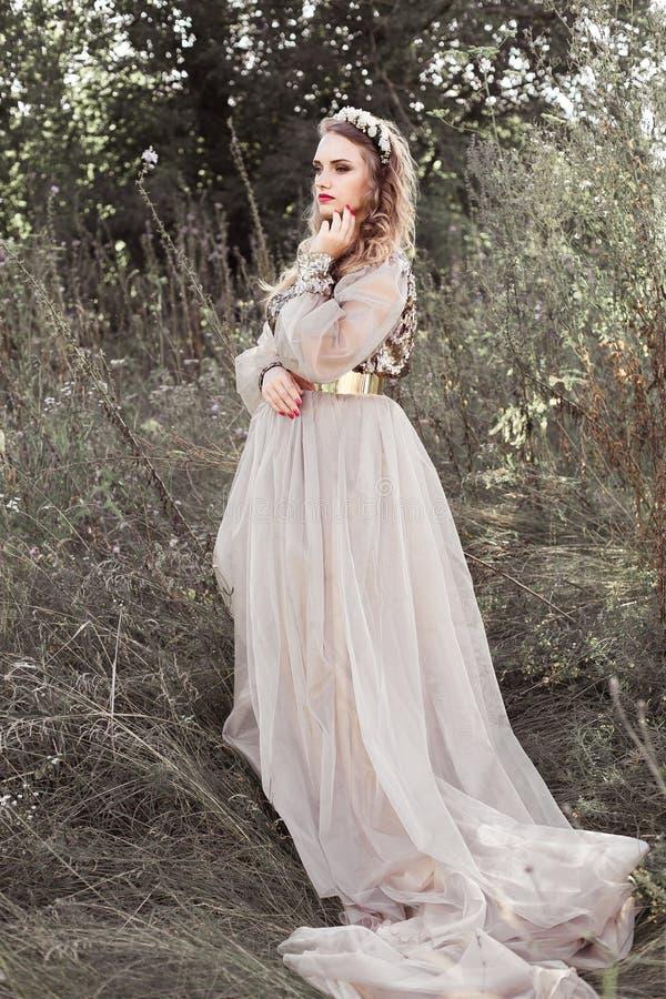 Jong mooi meisje in lange gouden kleding met lijn, met kroon van bloemen op haar hoofd in de lente groene tuin stock foto's