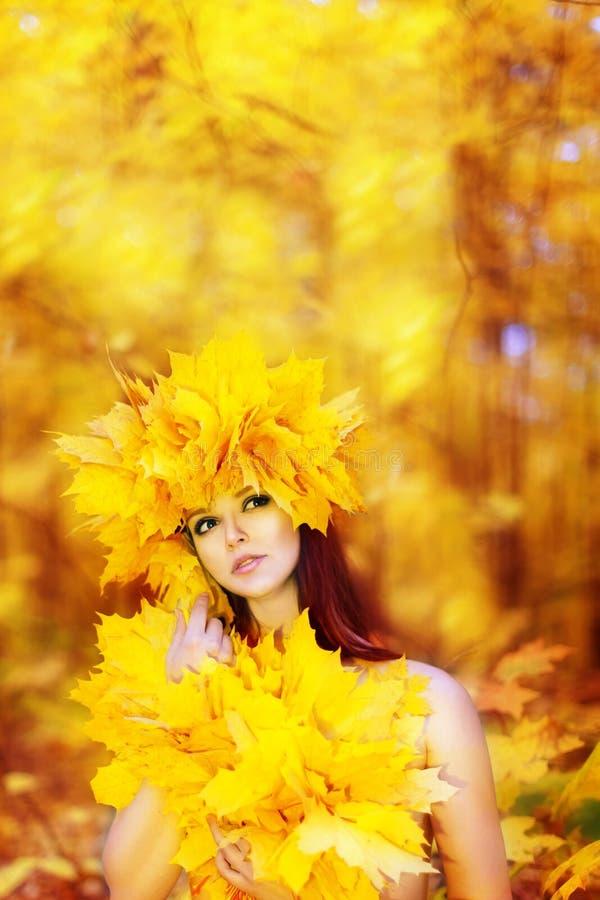 Jong mooi meisje met de herfstbladeren in zijn hand, en wre royalty-vrije stock afbeelding