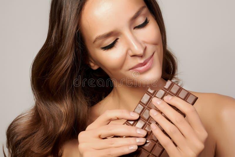 Jong mooi meisje met donker krullend haar, naakte schouders en hals, die een chocoladereep houden om van de smaak en a te geniete stock fotografie