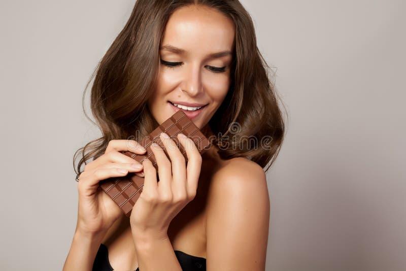 Jong mooi meisje met donker krullend haar, naakte schouders en hals, die een chocoladereep houden om van de smaak en a te geniete royalty-vrije stock foto's