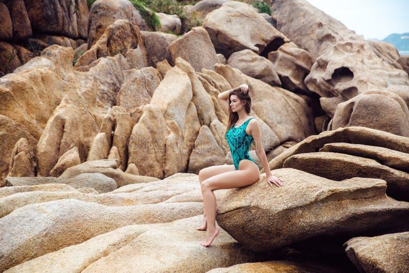 Jong mooi meisje met het uitstekende cijfer stellen op een tropisch strand Portret van sexy vrouw in blauwe swimwear bikini stock foto's