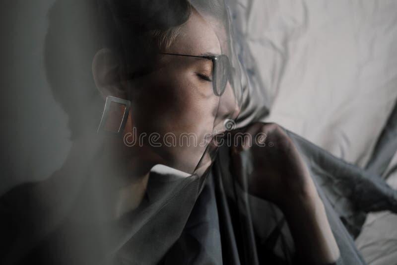Jong mooi meisje met kort krullend haar in glazen en zwarte vrijetijdskleding, studioportret royalty-vrije stock afbeelding