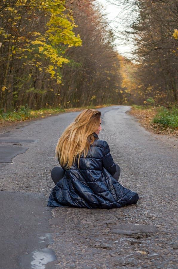 Jong mooi meisje met lange haarzitting op de asfaltweg in het de herfstbos stock foto