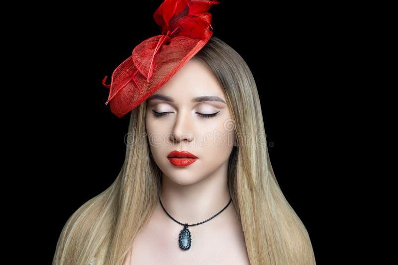 Jong mooi meisje met massieve rode bijkomende hoed royalty-vrije stock foto