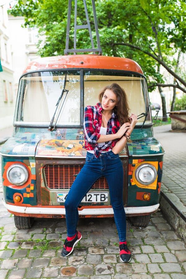 Jong mooi meisje in modieuze kleren voor het oude gebroken bus stellen in stadsstraat royalty-vrije stock foto