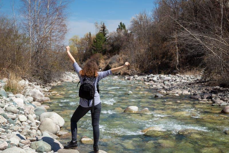 Jong mooi meisje op aard met een rugzak op de rivierbank Goede stemming op een heldere de lentedag Tegen de achtergrond van royalty-vrije stock afbeelding
