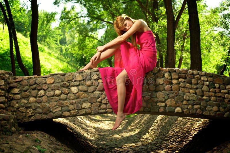 Jong mooi meisje op een steenbrug stock afbeeldingen