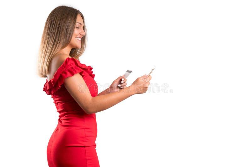 Jong mooi meisje in rode het kredietbard en telefoon van de kledingsholding Geïsoleerde stock fotografie
