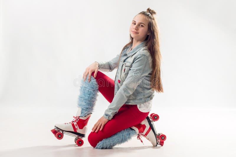 Jong mooi meisje in sportieve modieuze kleren met lang haar op vierwielige die rollen op achtergrond wordt geïsoleerd stock fotografie