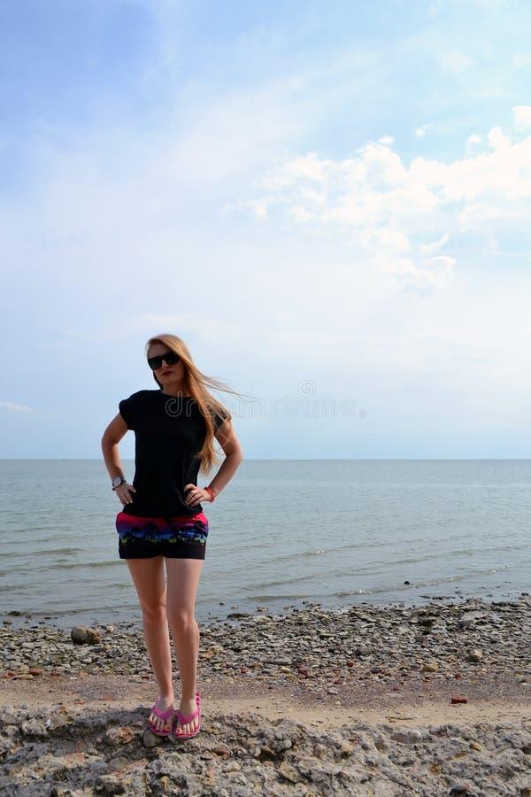 Jong mooi modieus meisje in het eenvoudige zwarte t-shirt stellen dichtbij het overzees stock foto