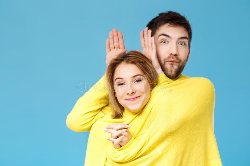 Jong mooi paar in één het gele sweater stellen die hebbend pret over blauwe achtergrond glimlachen stock afbeelding